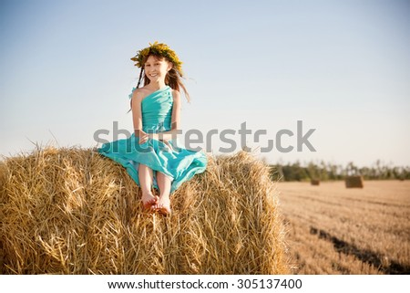 little girl sitting on a haystack - stock photo