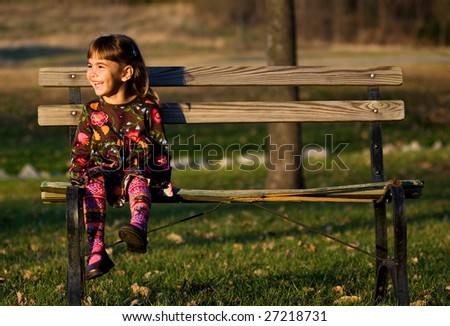 Little girl sitting on a park bench - stock photo