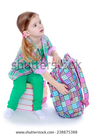 Little girl sitting on a pile of books to pack in a backpack. Isolated on white background studio photo. - stock photo