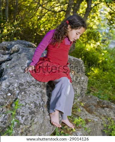 little girl sitting on a rock in the woods
