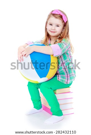 Little girl sitting on a stack of books and holding an inflatable striped ball- isolated on white background - stock photo
