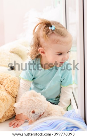 little girl sitting on a window sill and looking out the window, next to stuffed toys Teddy Bears