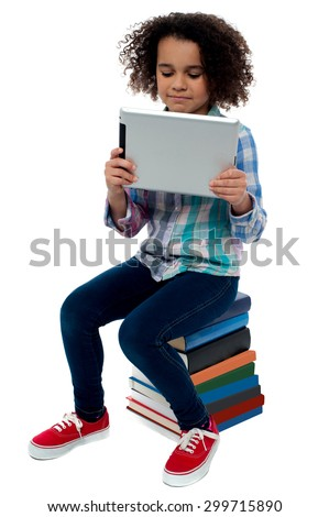 Little girl sitting on books with digital tablet - stock photo