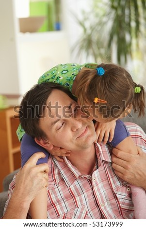 Little girl sitting on father's shoulders kissig his face. - stock photo