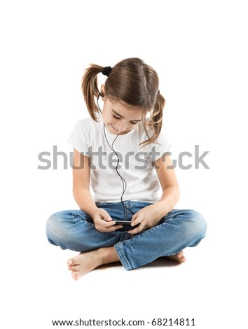 Little girl sitting on floor listen music with a MP3 player - stock photo