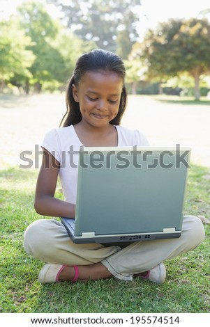Little girl sitting on grass using laptop on a sunny day