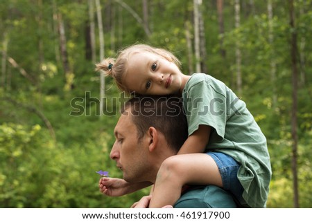 Little girl sitting on her father's shoulders
