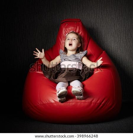 Little girl sitting on red beanbag - stock photo