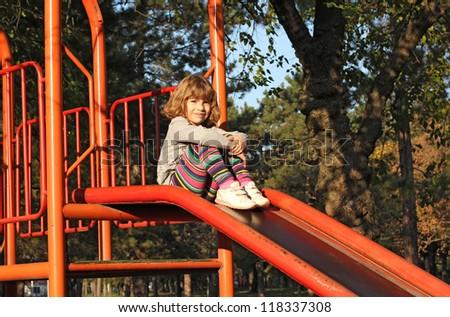 little girl sitting on slide - stock photo