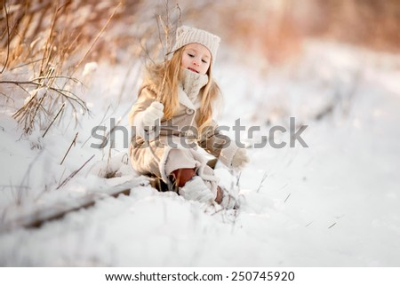 little girl sitting on snow in winter - stock photo
