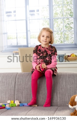Little girl sitting on sofa's back-rest at home, smiling, looking away. - stock photo