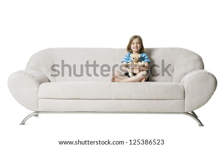 Little girl sitting on sofa with a teddy bear