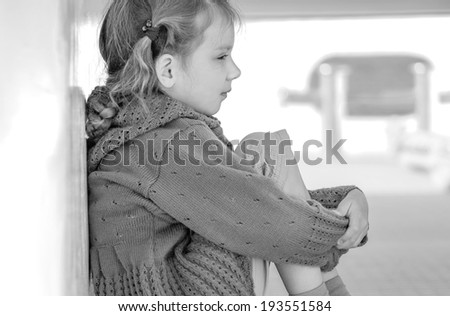 Little girl sitting on stern of ship step. - stock photo
