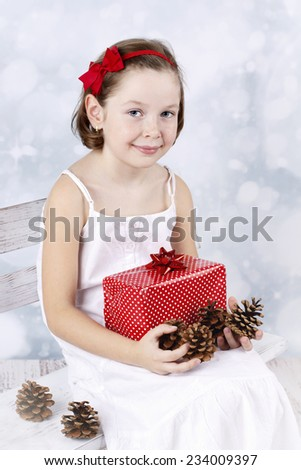 Little girl sitting on the bench and holding christmas present