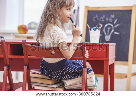 Little girl sitting on the chair and on the books at school in class. Training, education, preschool, will grow. - stock photo