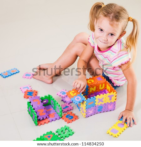 little girl sitting on the floor and building a house out of letters - stock photo