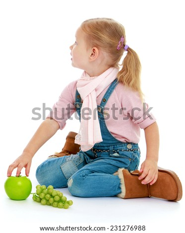 Little girl sitting on the floor and holding a hand an apple.Childhood education development in the Montessori school concept. Isolated on white background.