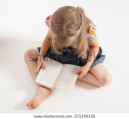 Little girl sitting on the floor and reading a book - stock photo