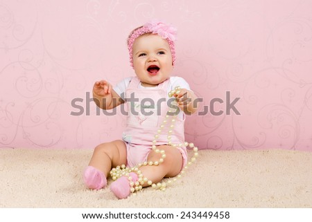 Little girl sitting on the floor holding a pearl necklace on pink background - stock photo