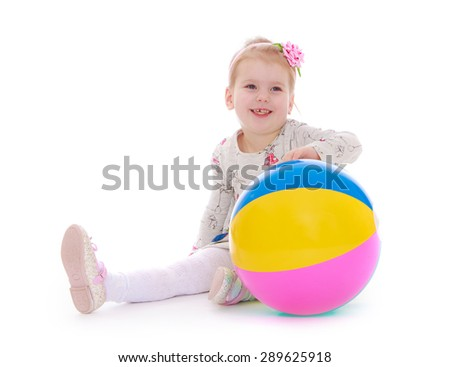 Little girl sitting on the floor next to the big ball - isolated on white background