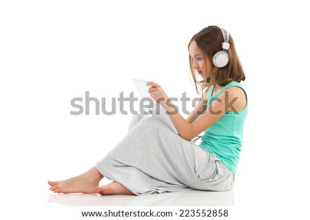 Little girl sitting on the floor, using a digital tablet and listening to the music. Side view. Full length studio shot isolated on white. - stock photo
