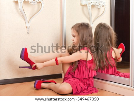 Little girl sitting on the floor, wearing adult shoes