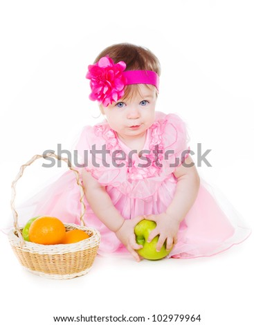 Little girl sitting on the floor with basket of green apples and oranges on white background. - stock photo