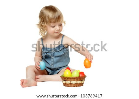 Little girl sitting on the floor with Easter eggs, isolated on white background