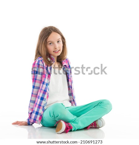Little girl sitting on the floor with legs crossed and looking at camera. Full length studio shot isolated on white.