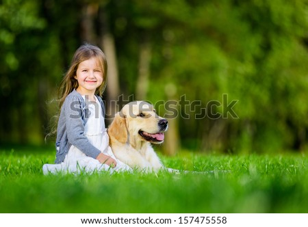 Little girl sitting on the grass with labrador retriever in the summer park - stock photo