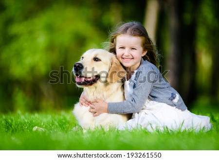 Little girl sitting on the green grass with labrador retriever in the summer park - stock photo