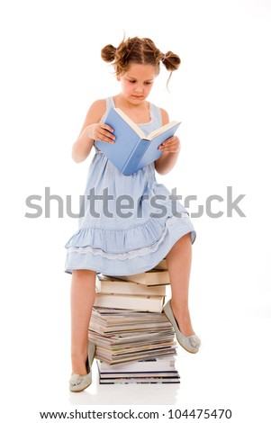 Little girl sitting on the heap of books and reading one of them - stock photo