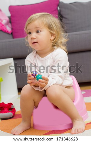 Little girl sitting on the potty at home.