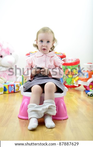little girl sitting on the potty with a remote control (or mobile phone) in hand - stock photo