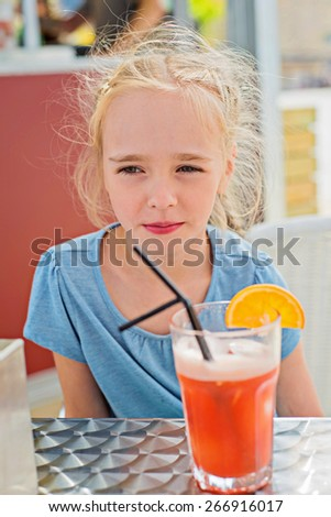 Little girl sitting on the table and drinking orange juice