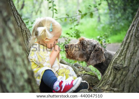 Little girl sitting on the tree  and playing with her dog in the wood on a sunny spring day. Best friends concept.Positive emotions.Outdoor activity and game with family pet on summer holiday. - stock photo