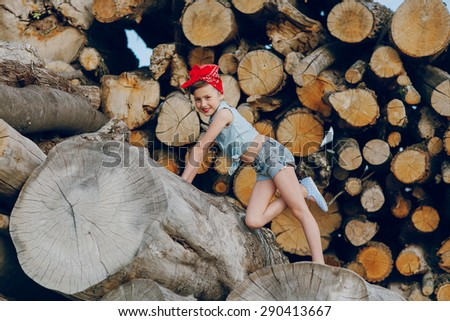 little girl sitting on the wood style pin up in jeans clothes