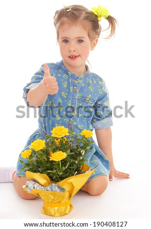 Little girl sitting with a bouquet of yellow roses and shows thumb up