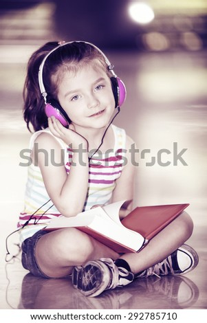 Little girl sitting with books and headphones - stock photo