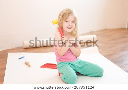 Little girl sitting with tools in his hands. Apartment repair. Wallpapering. Stock Photo - stock photo