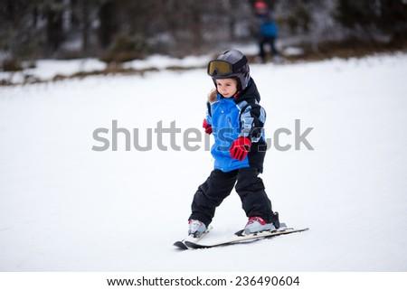 Little girl skiing down the ski slope - stock photo