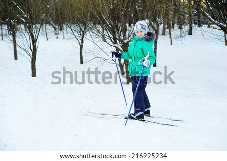 Little girl skiing on cross country skis in the forest on the perfect winter day - stock photo
