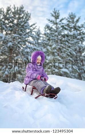 Little girl sledding in the winter day - stock photo