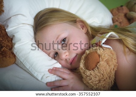 Little girl sleep in bed with teddy bear