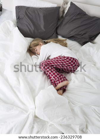Little Girl sleeping in a big bed - stock photo