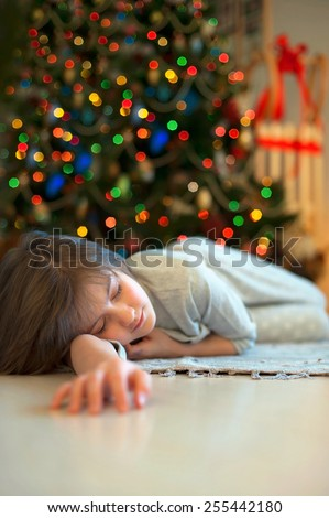 Little girl sleeping near illuminated new-year tree dreaming about christmas miracles. - stock photo