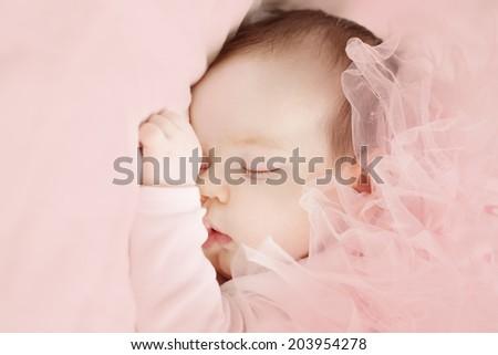 Little girl sleeping on light pink background - stock photo