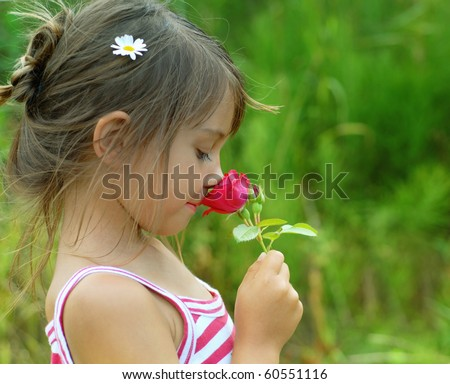 Little girl smelling a red rose - stock photo