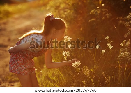 Little girl smelling a wild flower in summer - stock photo