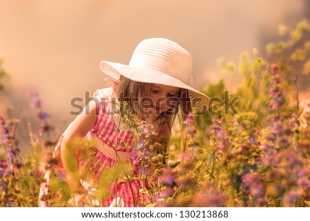 Little girl smelling flowers in the meadow - stock photo